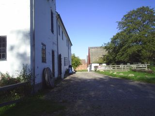 Esrum Møllegaard. The main millbuilding with a millstone in front, ecxibition- and education building at rigtht and Esrum Kloster ( Monastery) back in the picture. building