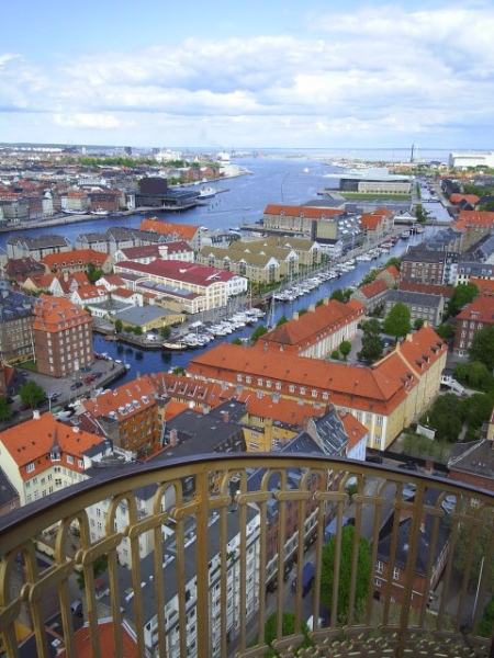 """Vor Frelsers kirke på Christianshavn. View from the top of the Church """"Our Savier"""", 90 m over sealevel. View in direction Copenhagen Inner harbour with  The New Royal National Theatre""""at the waterline up/left in the picture. In the background Amaliehaven, kastellet ,Langelinie , trekroner fort and Navy base Holmen and The New Royal Opera. In front af teh picture Christianshavn med canals builsd od King Christian 4. in 1620´erne. Photo: 9. may 2009."""